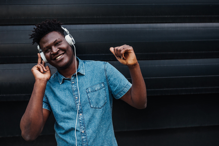 A man is smiling and wearing headphones