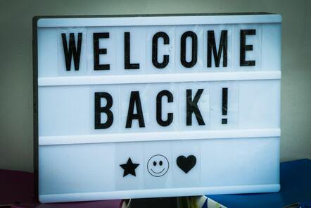 Sign reading welcome back with a star, smiley face, and heart icon