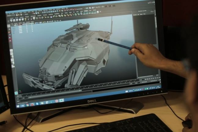 A developer's hand points to a graphic of a military vehicle being created on their computer