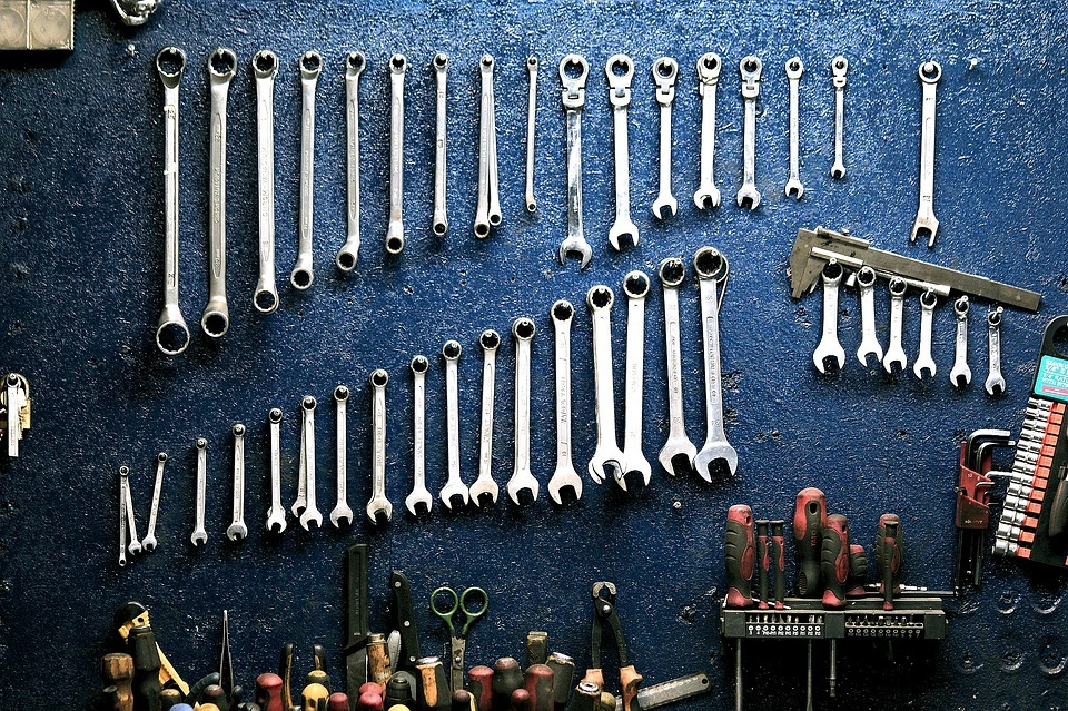 A collection of mechanical tools, including spanners, hanging up in a workshop.