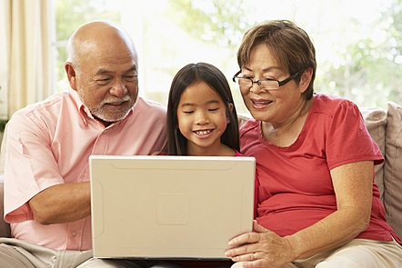 child and two adults looking at a laptop