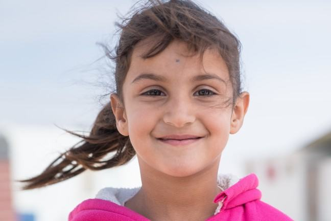 Young unaccompanied girl, 7 years old, with a pink hooded sweatshirt is smiling into the camera.