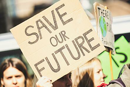 A photo of a woman holding a sign saying save our future