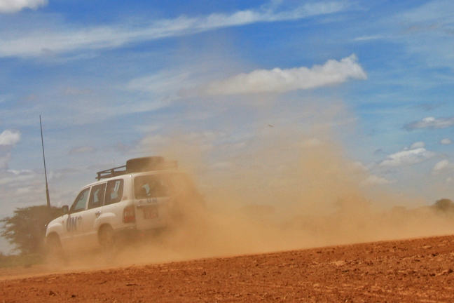 Image of jeep driving away with dust