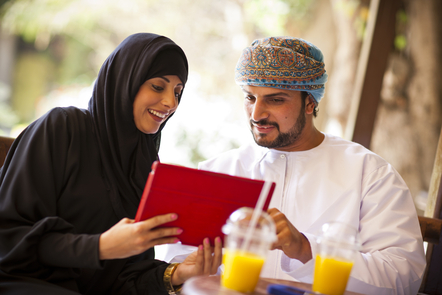 a man and a woman looking at a tablet