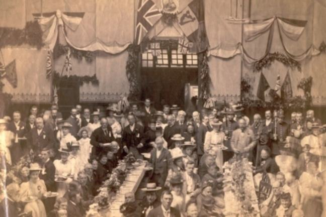 Black and white photo of many people sat at or stood beside long tables featuring tea