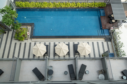 A swimming pool, with umbrellas, private gardens and amenities surrounding it.