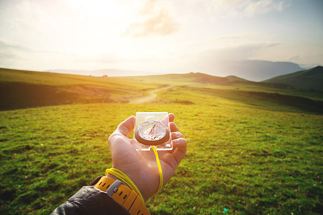 hand with a magnetic compass ea against the backdrop of a beautiful landscape at sunset.