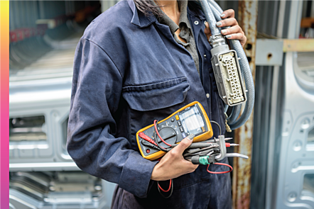 A woman in overalls holding electrician equipment .