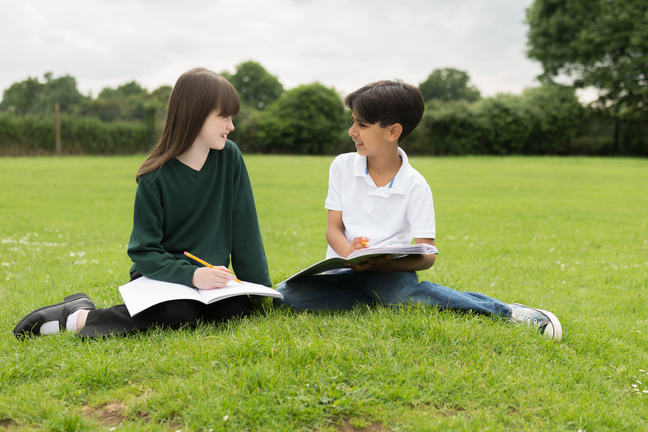 two students writing in books on a grass lawn