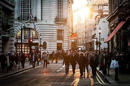 La imagen muestra una calle de la ciudad con mucha gente caminando. Parece ser la puesta de sol de un día de invierno, con gente con bufandas y abrigos. Parece ser un área comercial, debido a los letreros de las tiendas y a la gente que lleva bolsas.