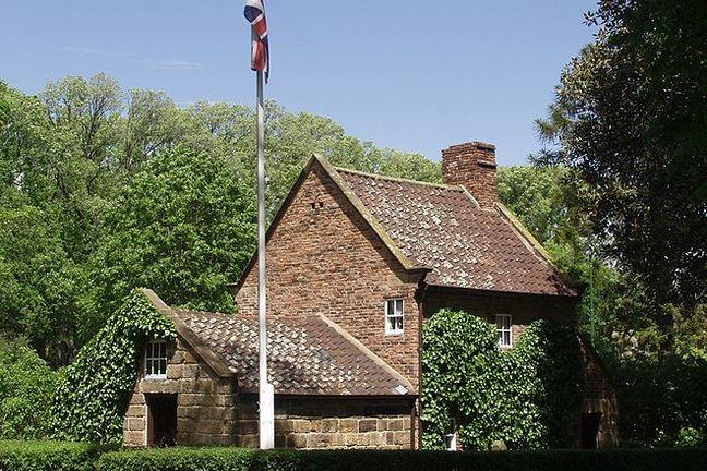 Photo of Cook's cottage, Melbourne, a redbrick cottage covered in ivy set in trees with flagpole outside carrying union jack