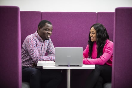 Two people smiling and watching something on a laptop