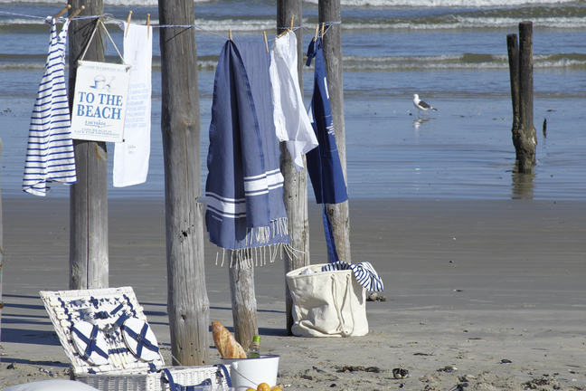 An image of a beach with blue and white textiles on display