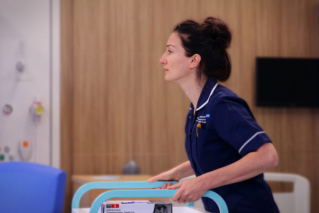A stressed nurse in a ward pushing a trolley.