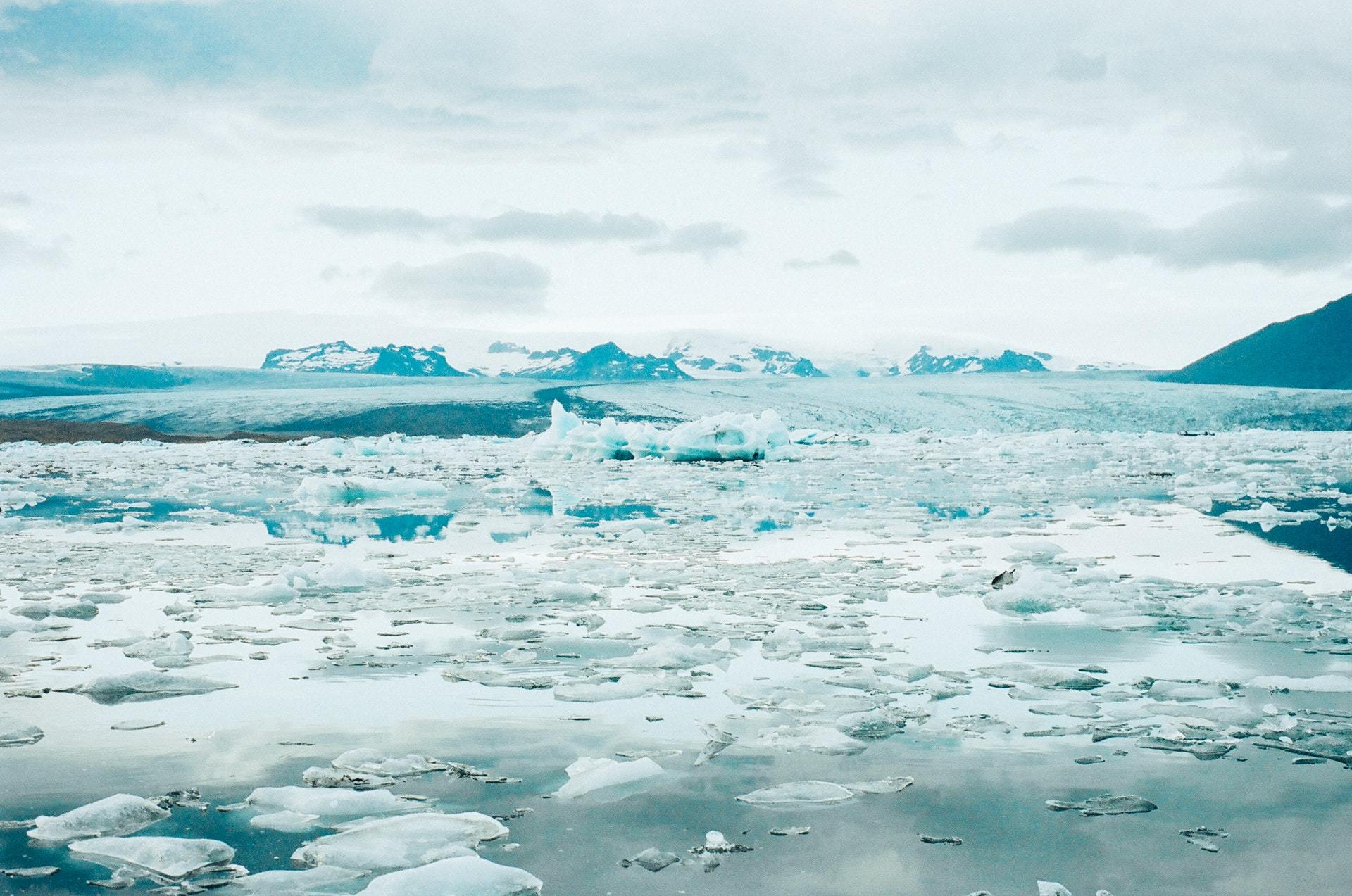 View over an expanse of water with fragmented broken ice against a backdrop of icy mountains