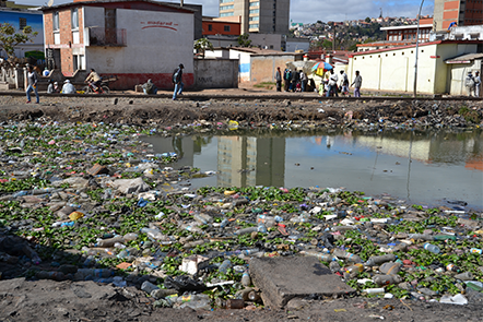 Polluted river with plastic bottles