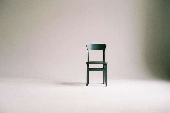 Empty room with a single wooden chair