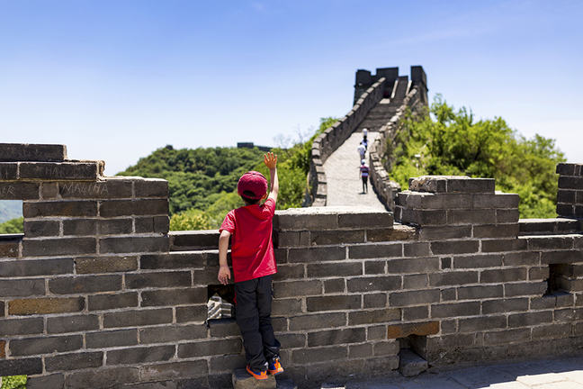 boy waving while standing on the Great Wall of China