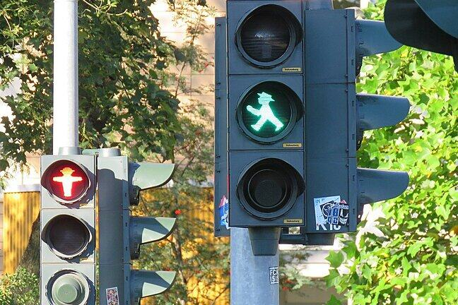 Two sets of pedestrian crossing lights, both apparently for the same crossing, one is green for go, but the other is red for stop