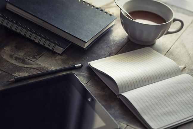 Image of a notepad, ipad and coffee on a desk