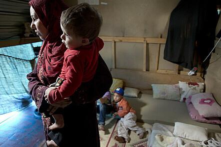 Refugee woman holding toddler.