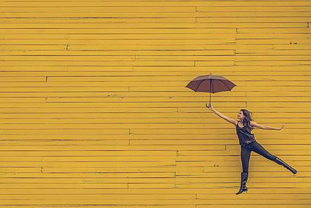 Lady jumping with an umbrella against a yellow background