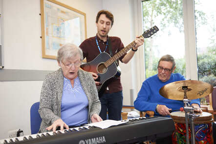 An elderly woman is playing an electric keyboard while a male music therapist is standing behind her playing an acoustic guitar and a man is seating playing the drums to the right