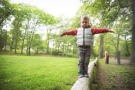 A boy balanced on a tree playing in a park.