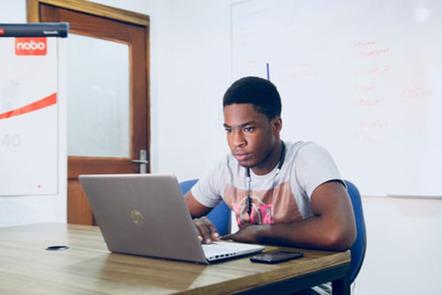 Man in t-shirt working on laptop