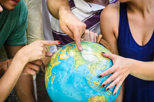 Image of hands pointing to different places on a globe
