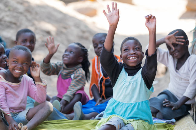 A girl with cerebral palsy sits with friends. She has her hands in the air as she smiles