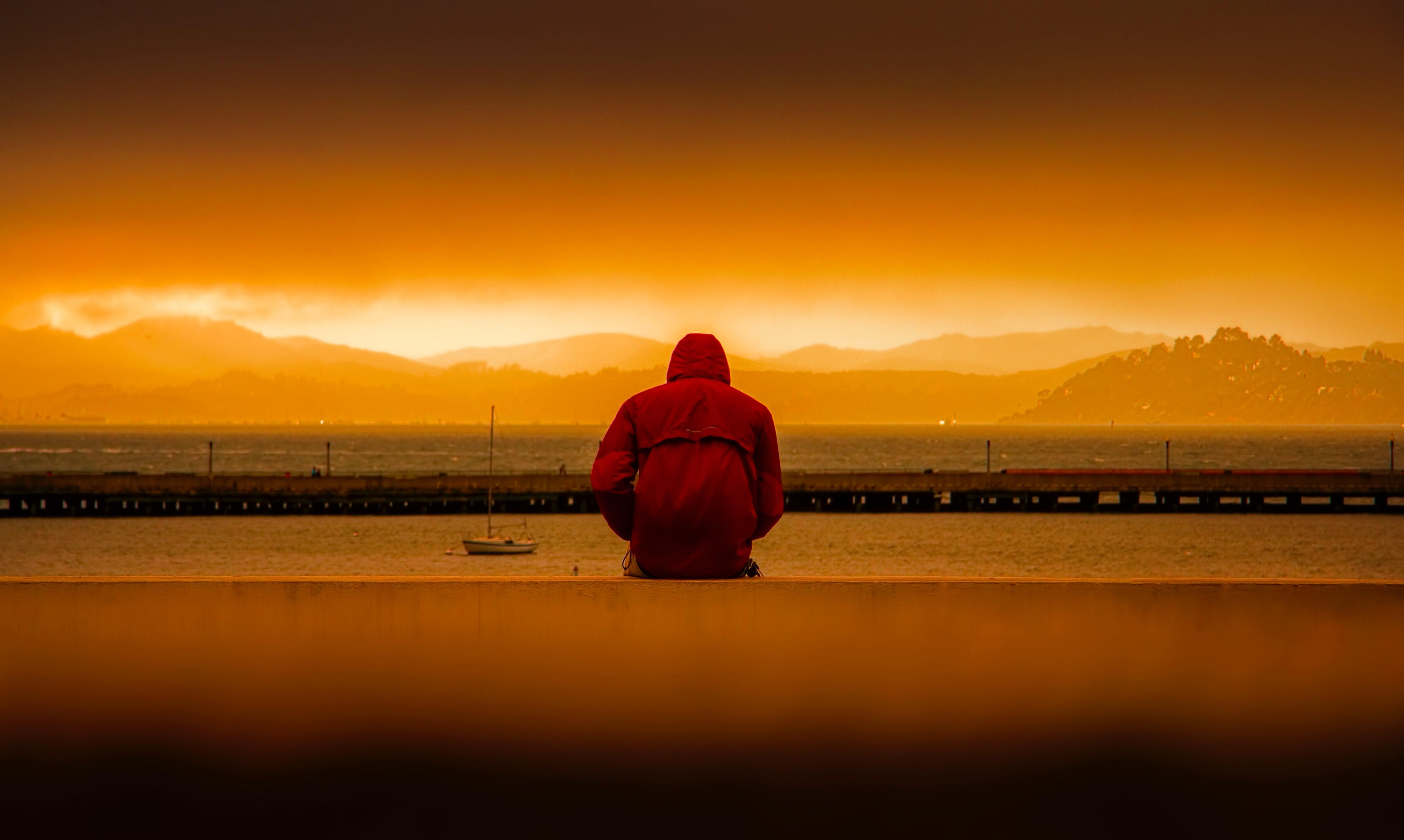 A person sitting alone on the waterfront.