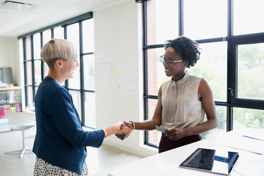 Female architects handshaking in office