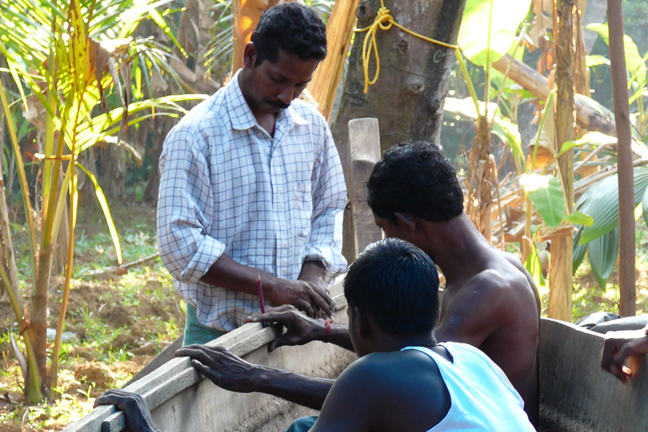Two boat builders and an apprentice working on a tied or 'stitched' plank boat