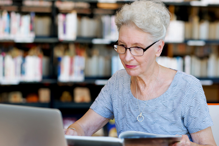 A woman with white hair wearing glasses is studying from a laptop