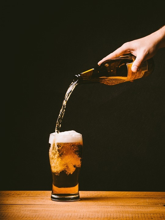 Pouring a bottle of beer into a pint glass.