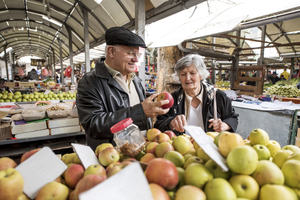 A man and woman buying fruit from a market stall