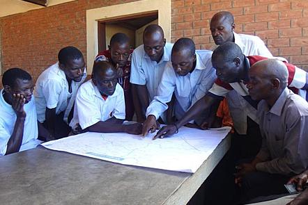 A group of 9 men from Mozambique wearing white shirts gather around a map on a table. Several of the men are pointing at this map.