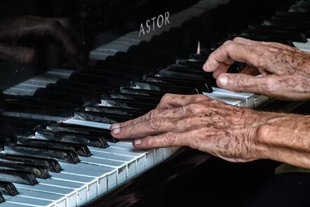 A pair of elderly hands plays the keys on a piano