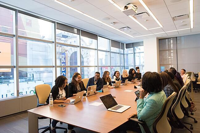 A board room in an office with large windows. The table is full, 7 people each side mostly Black women