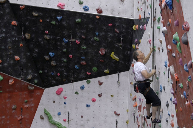 An older person at a climbing wall