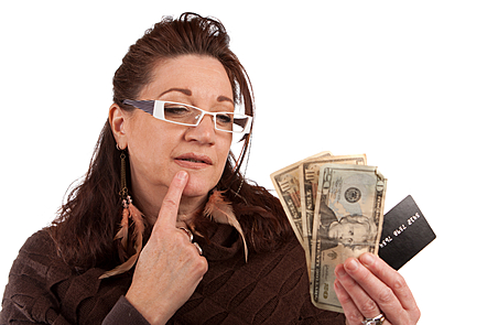 Middle aged woman carefully looking at cash and a credit card in her hand.