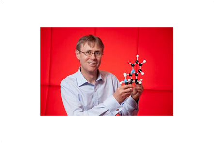 a photo of David Manallack holding a model of a molecule
