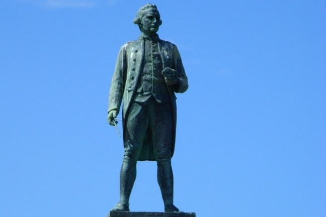 Captain Cook statue, Whitby, with Cook standing partially in shadow against blue sky background.