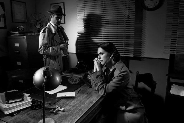 Pensive woman being interviewed at desk by detective in a noir setting