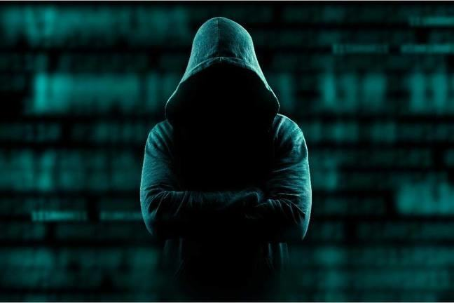 Hacker in a hoodie against a dark background of code.