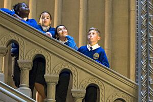 Four children from the Colonial Countryside project leaning on a bannister on a staircase at Penrhyn.