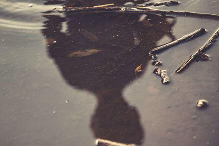 Child's reflection in a puddle