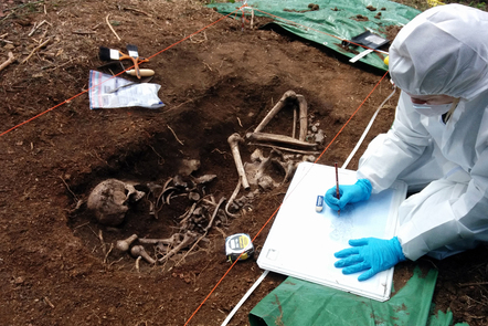A forensic scientist examines human remains in an open grave, in order to identify the dead